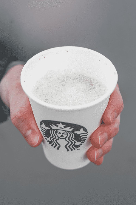 A hand holding a cup of Starbucks espresso macchiato.