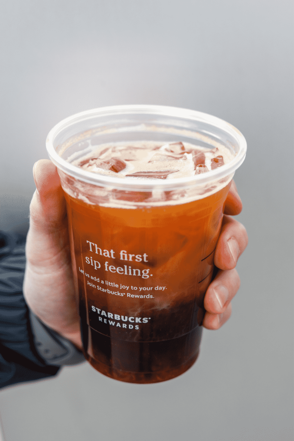 A hand holding a cup of Starbucks iced shaken espresso.