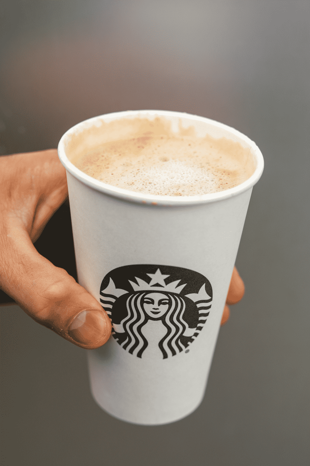 A hand holding a cup of Starbucks keto blonde vanilla latte.