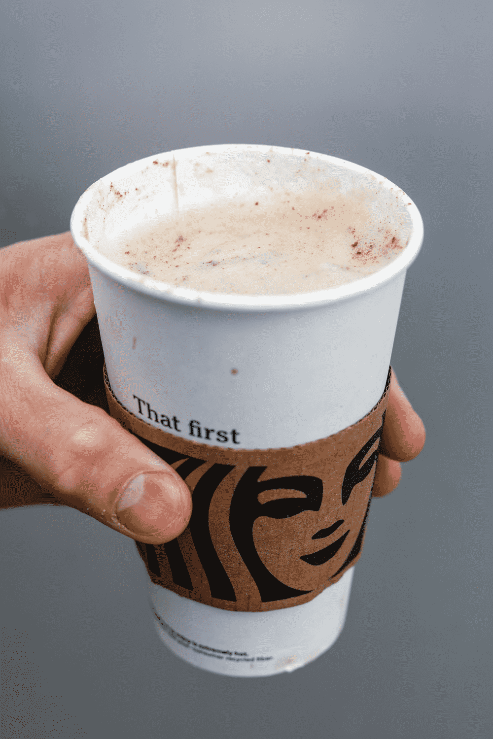 A hand holding a cup of Starbucks keto cinnamon dolce latte.