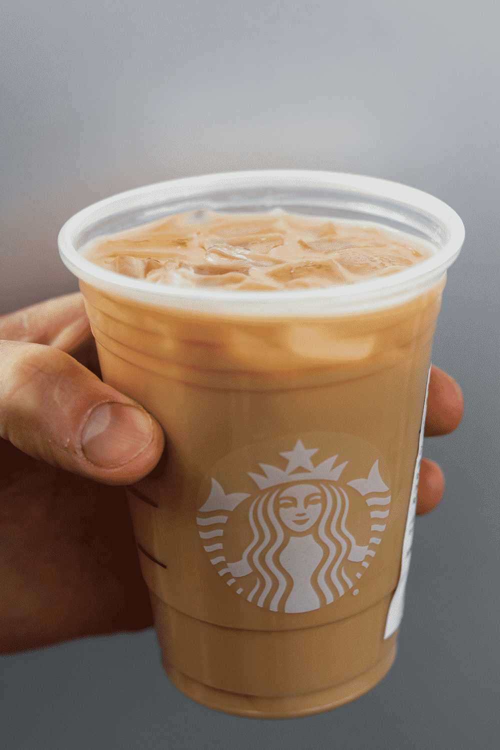 A hand holding a cup of Starbucks keto iced blonde vanilla latte.