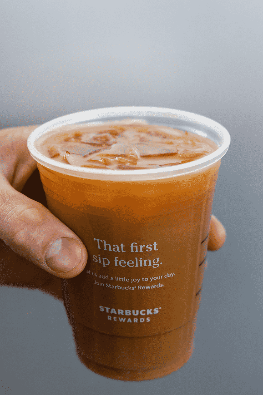Hand holding a cup of Starbucks keto iced flat white.
