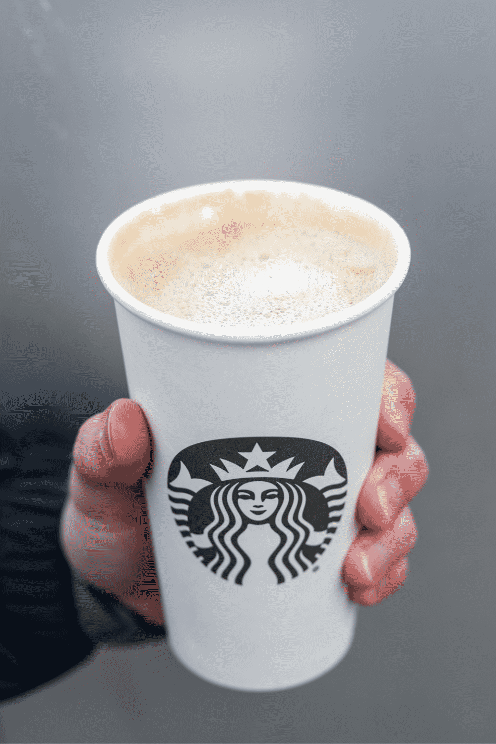 A hand holding a cup of Starbucks blonde vanilla latte.