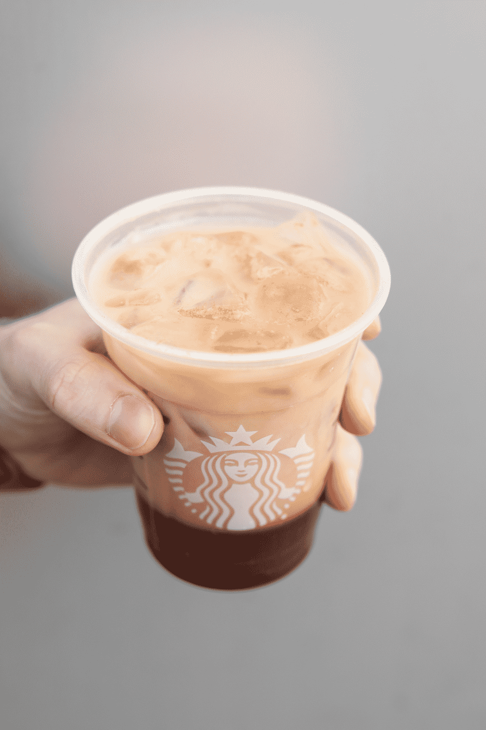 A hand holding a cup of Starbucks chocolate almond milk espresso.