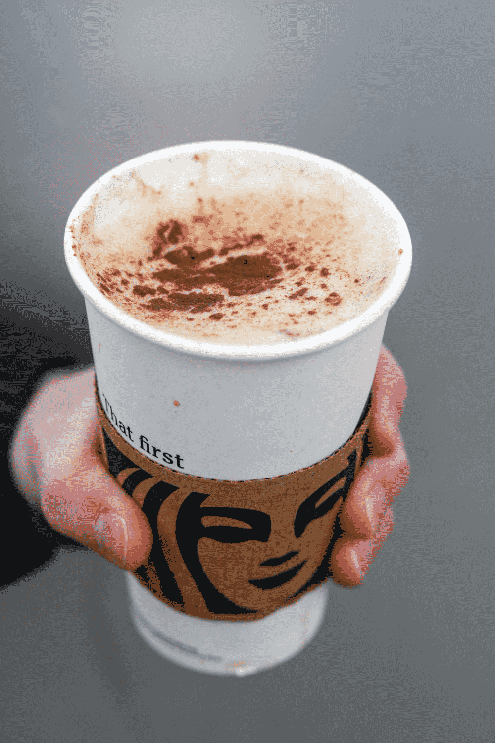 A hand holding a cup of Starbucks cinnamon dolce latte.