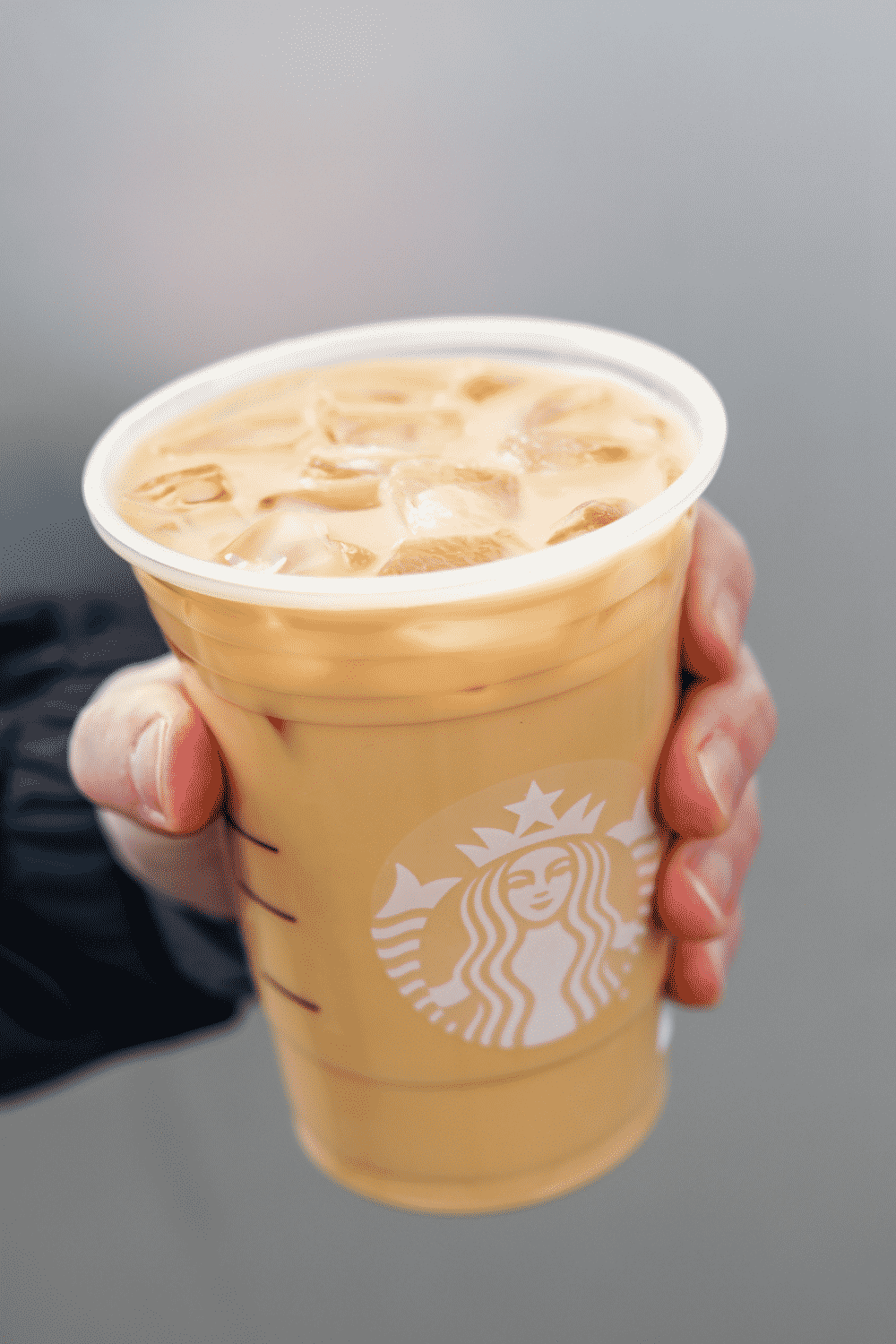 A hand holding a cup of Starbucks iced blonde vanilla latte.