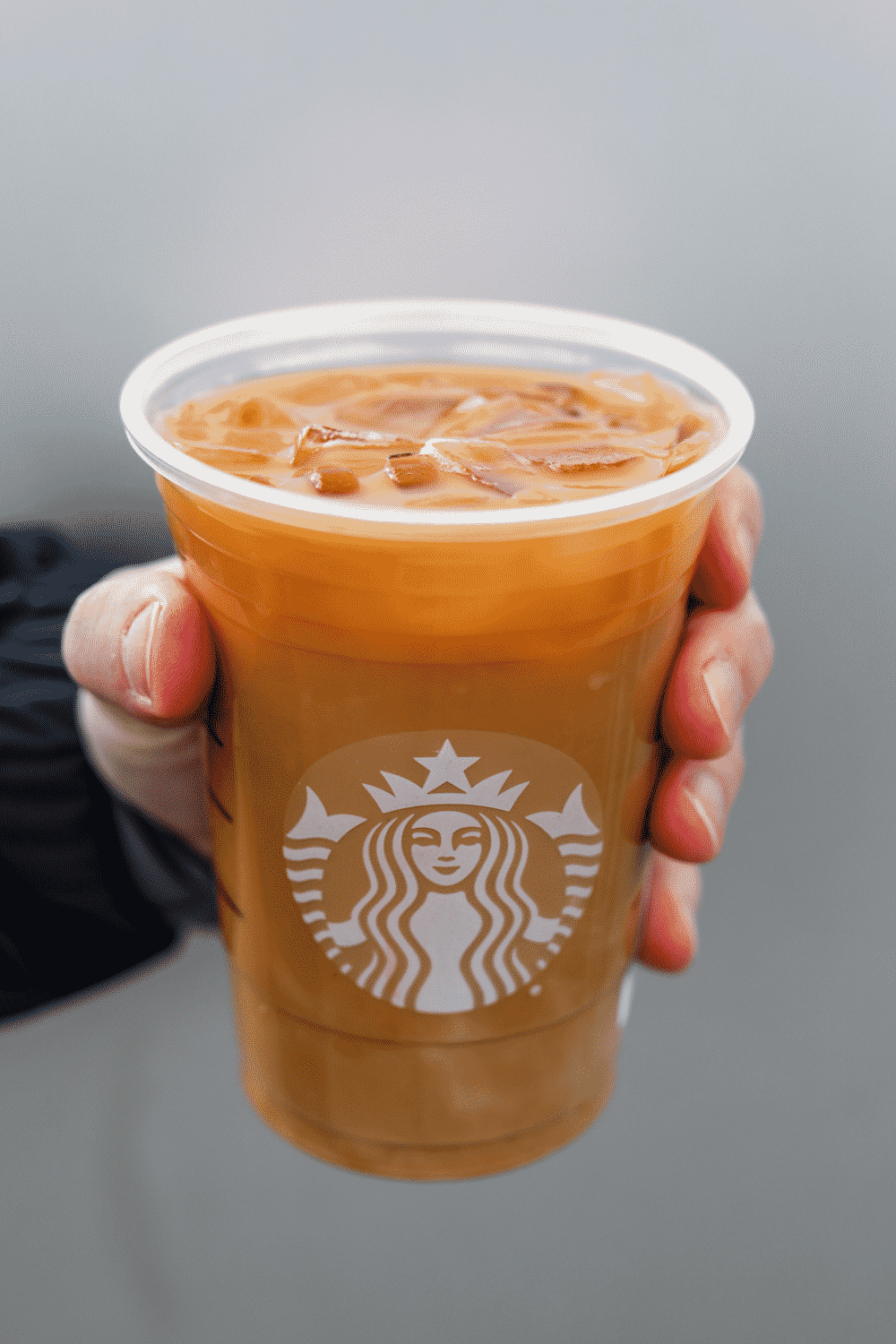 A hand holding a cup of Starbucks iced flat white.