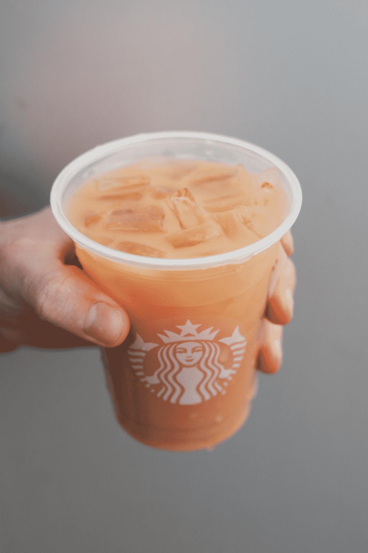 A hand holding a cup of Starbucks iced London fog tea latte.