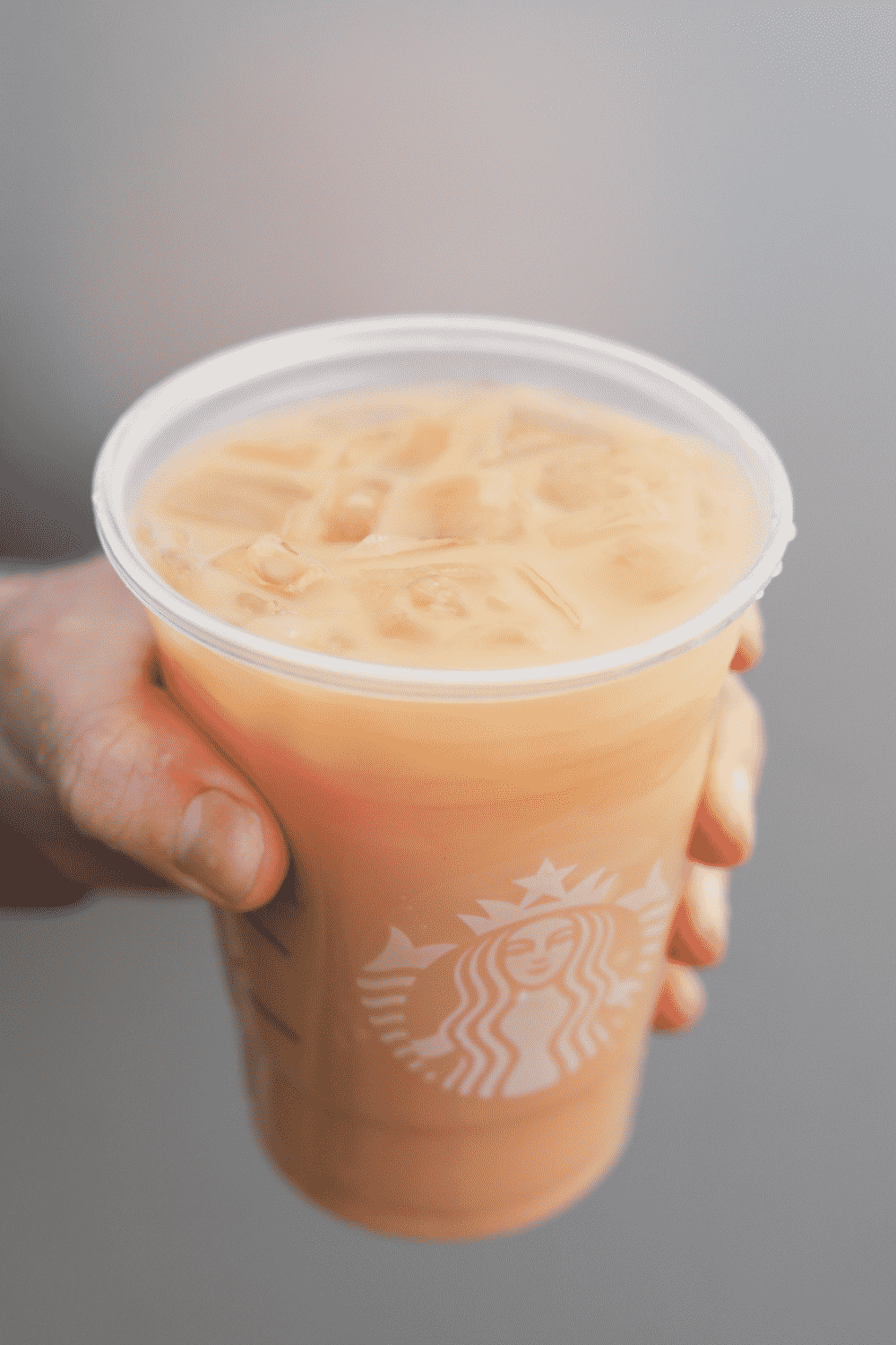 A hand holding a cup of Starbucks iced royal English breakfast tea latte.