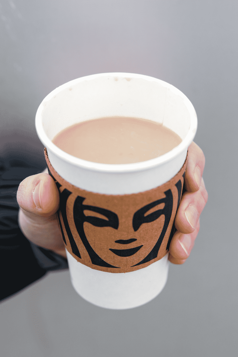 A hand holding a cup of Starbucks latte with almond milk.