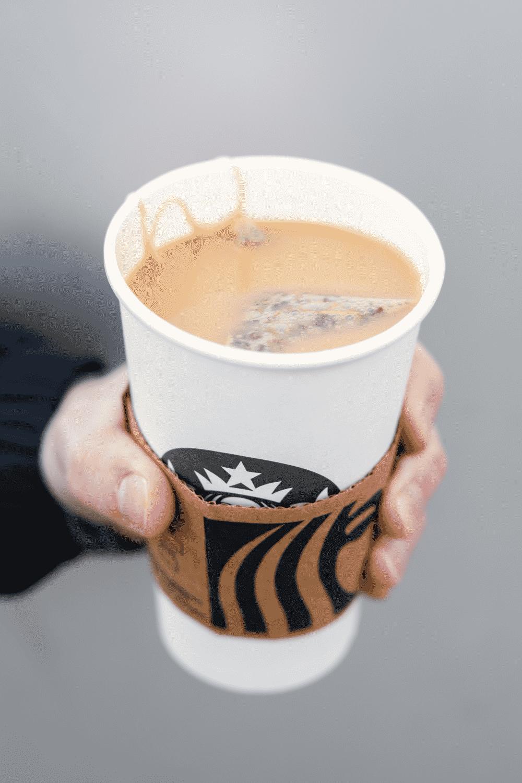 A hand holding a cup of Starbucks London fog tea latte.