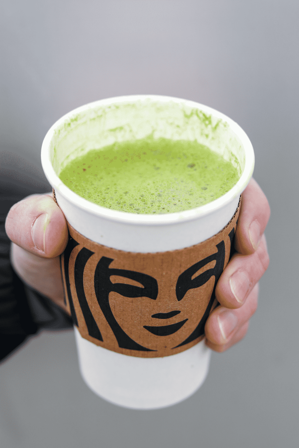 Hand holding a cup of Starbucks matcha latte.