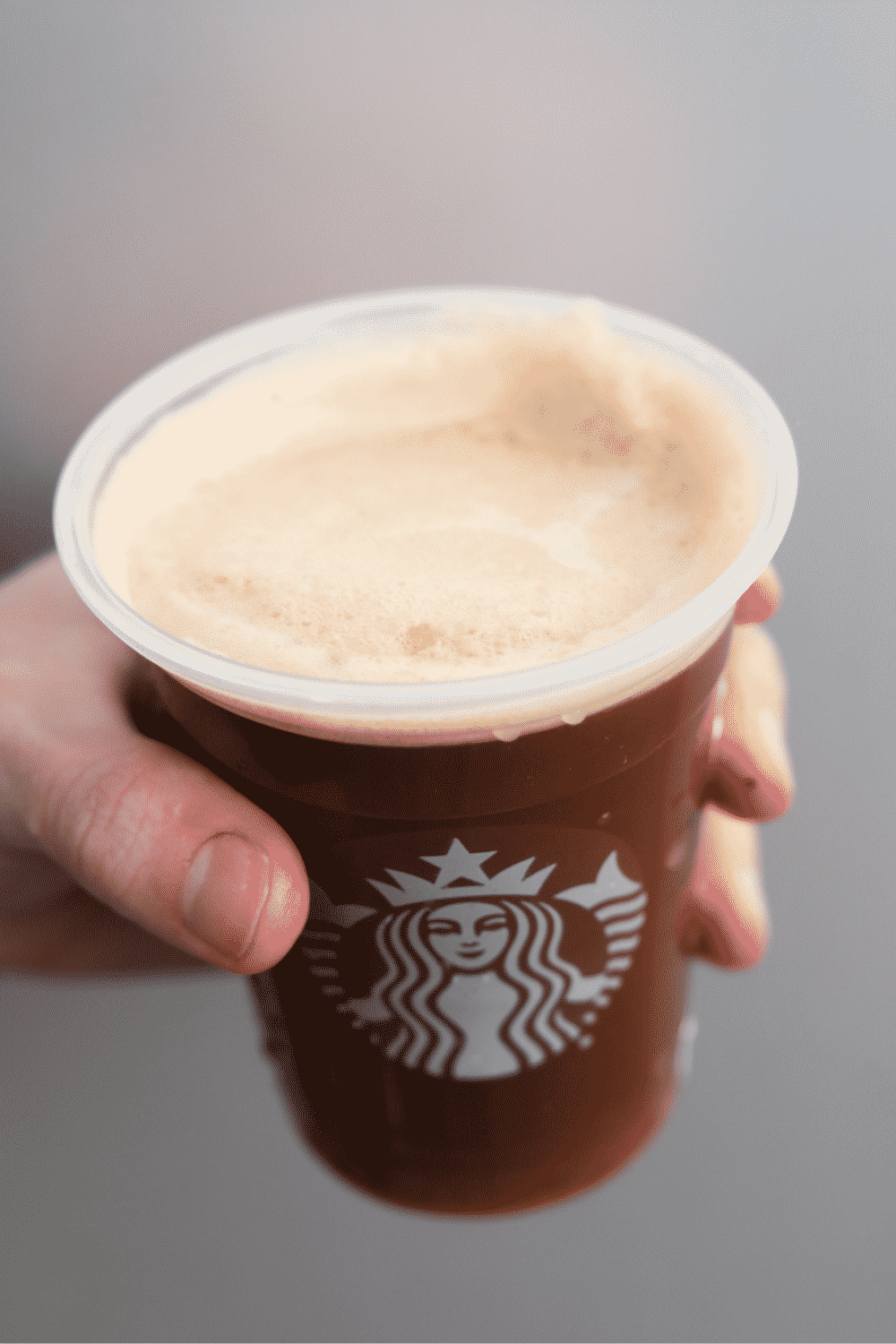 Hand holding a cup of Starbucks iced nitro cold brew.