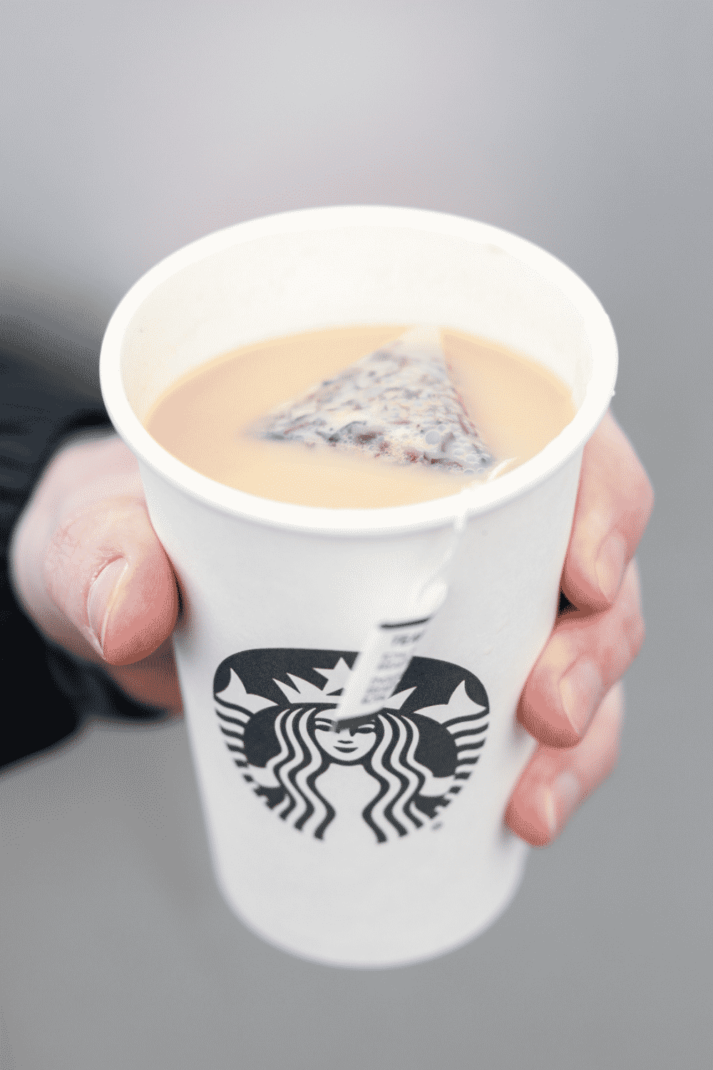 A hand holding a cup of Starbucks royal English breakfast tea latte.