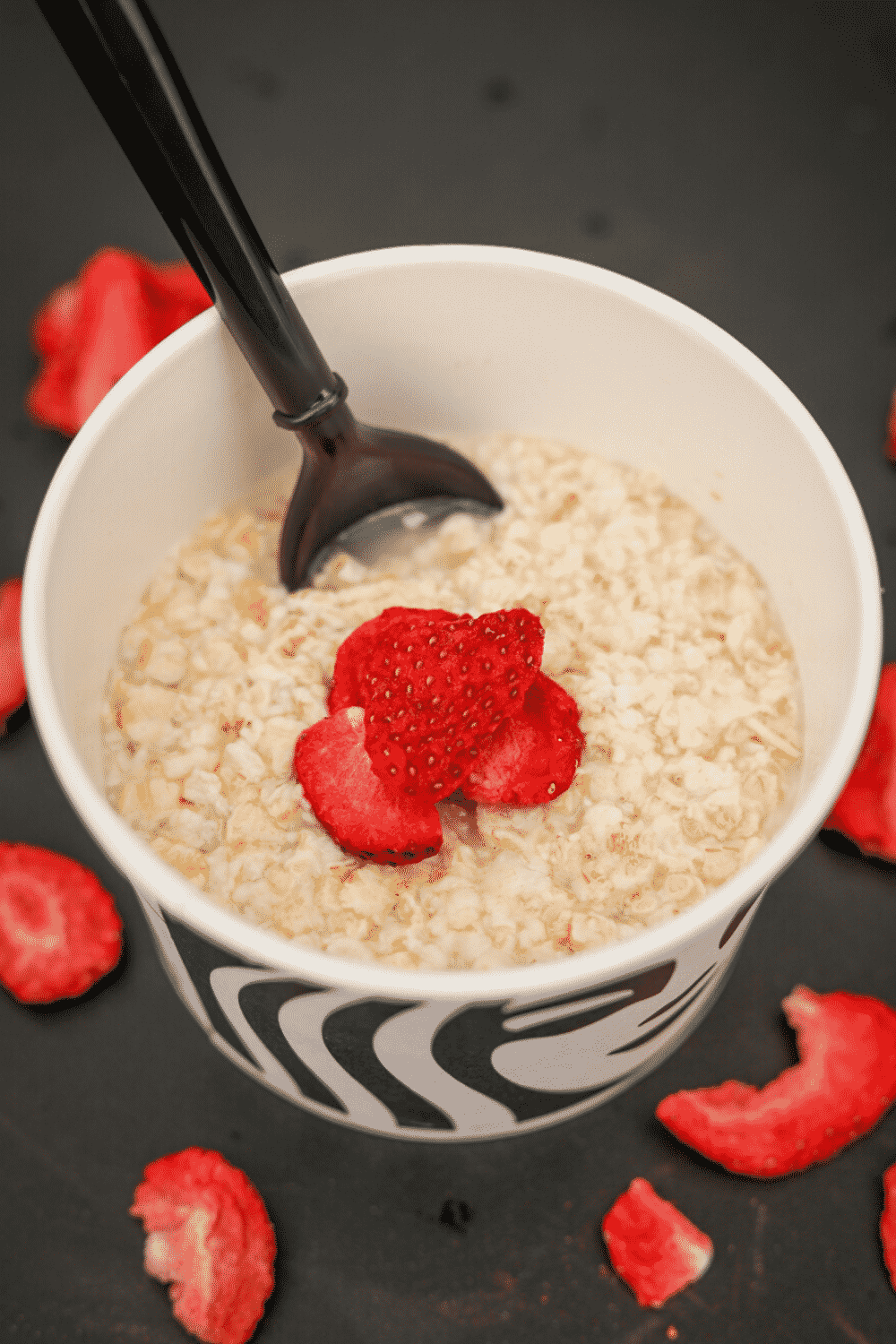 A cup of Starbucks oatmeal with a few freeze dried strawberries on top.