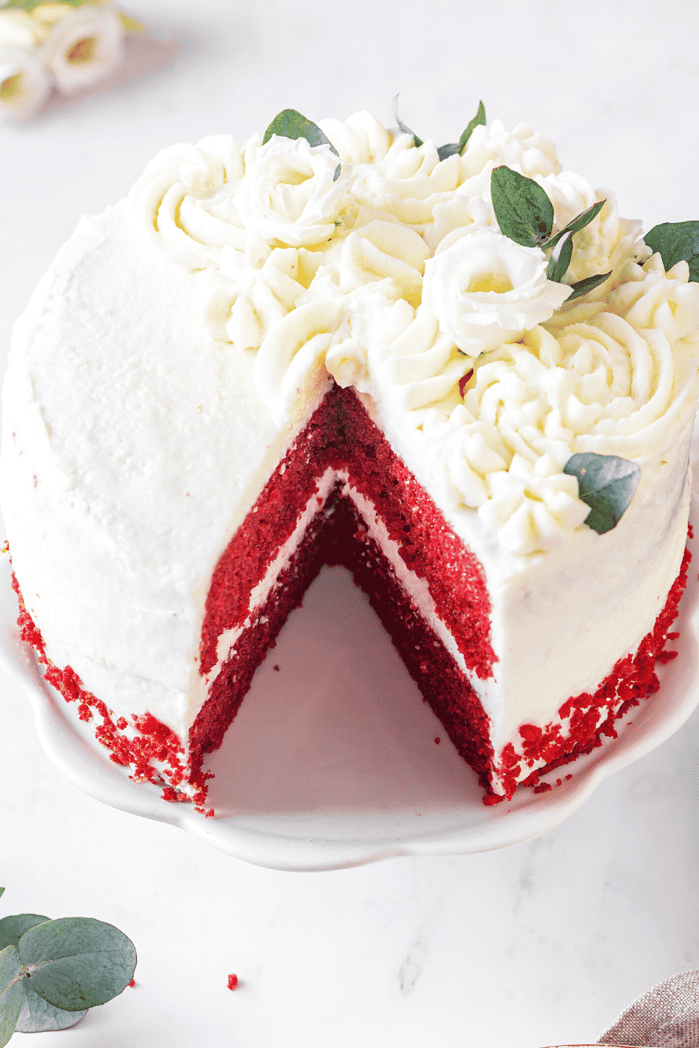 A red velvet cake on a white serving tray. A piece of cake is missing from the front of the cake.