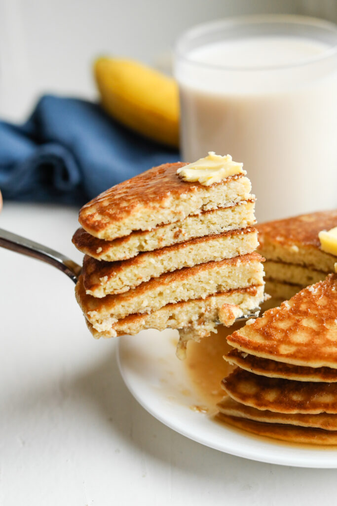 A fork holding a stack of cut up pancakes. The pancakes are topped with butter and there is a glass of milk, and a blue napkin behind them.