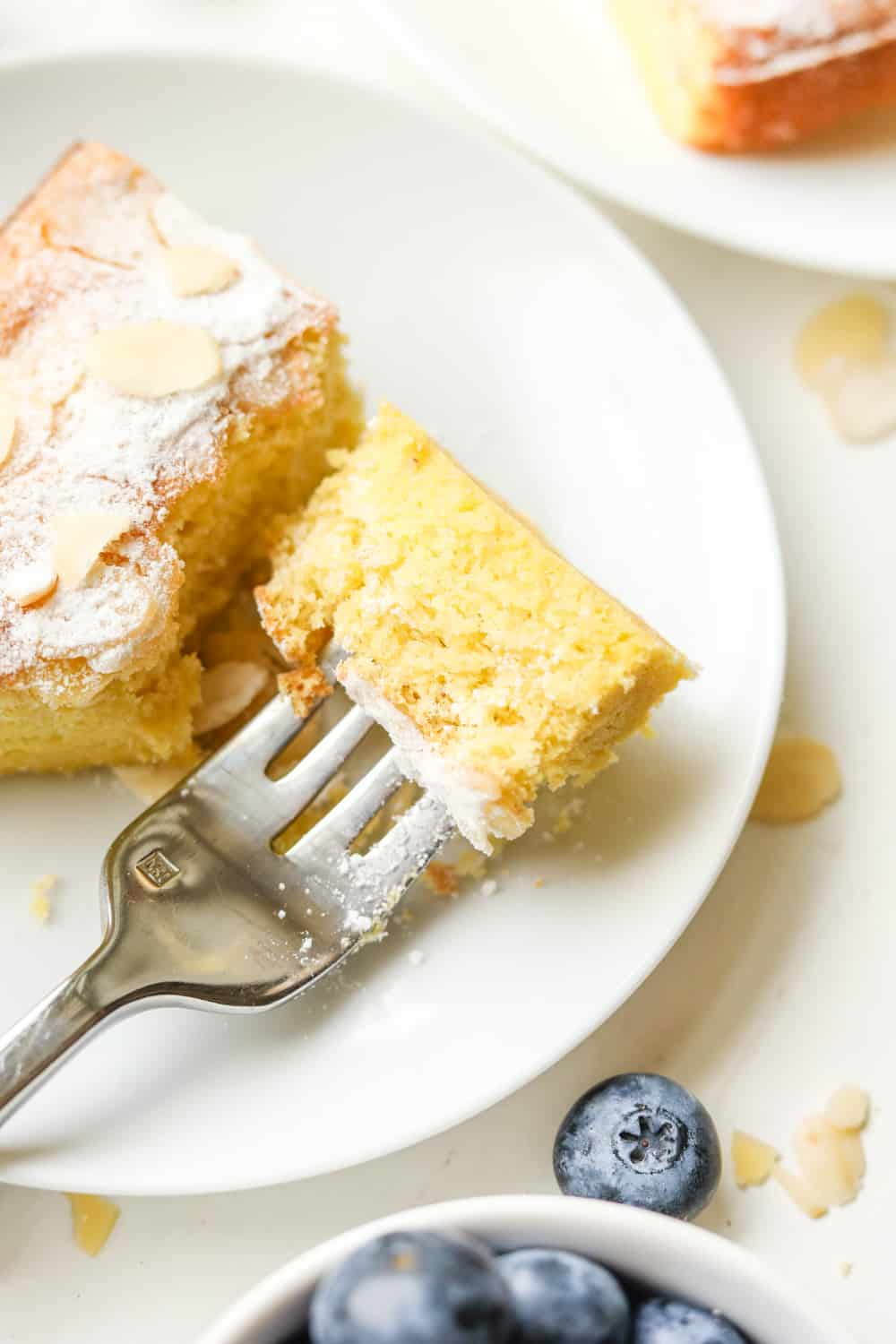 A piece of almond cake on a white plate with a fork holding a piece of the cake.
