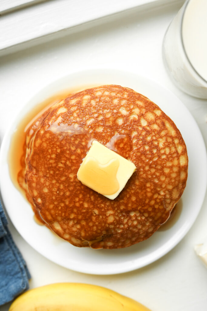 A stack of pancakes topped with butter and maple syrup.
