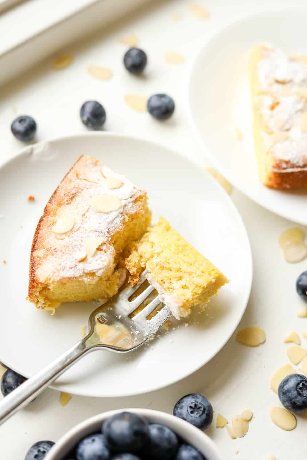 A slice of almond cake on a white plate, and a fork is holding a piece of the cake. There's a cup of blueberries next to the plate as well as some loose ones.