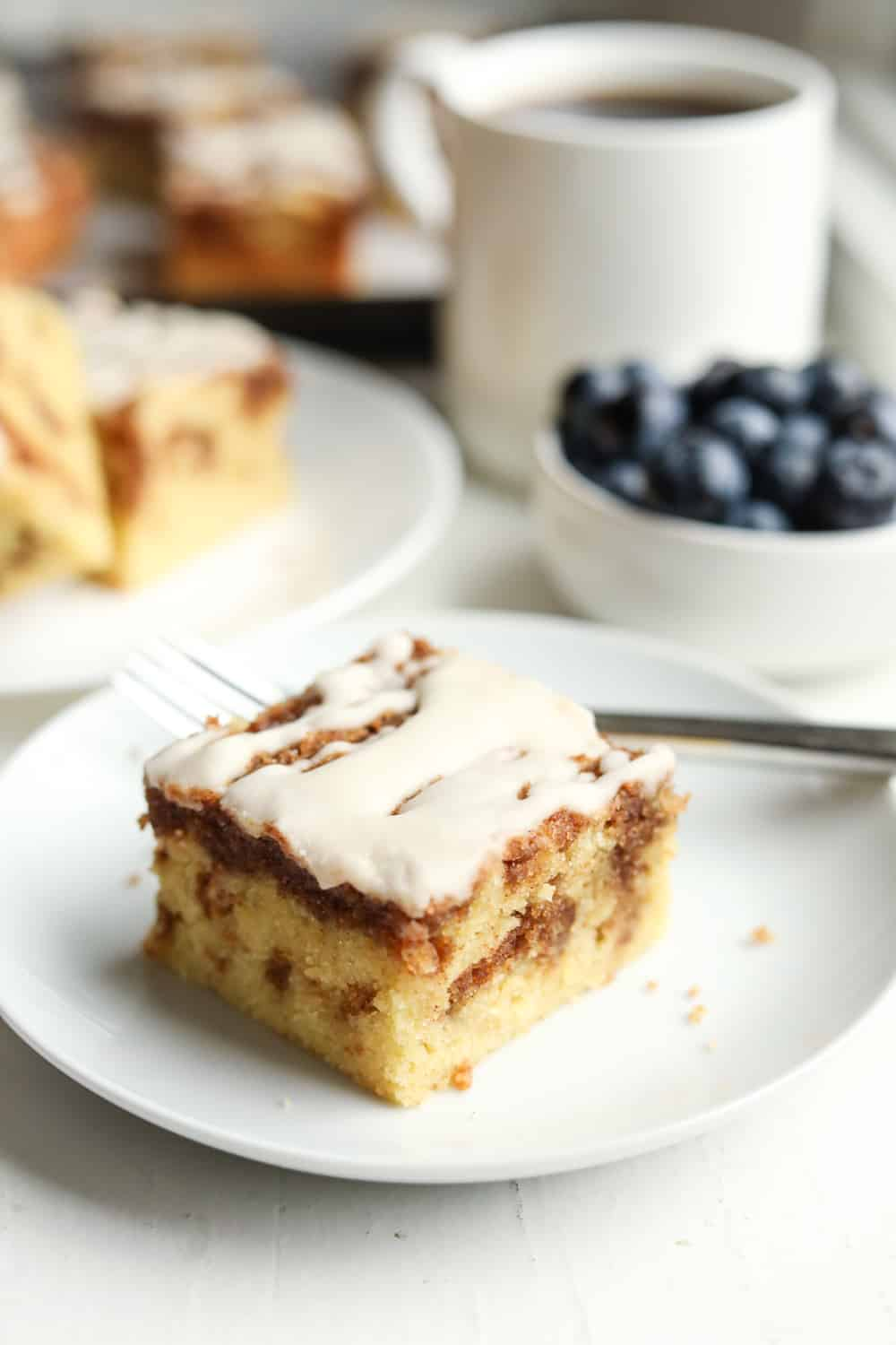 A piece of coffee cake on a white plate with a fork set by it. There's a coffee cup, blueberries, and more pieces of cake set behind the plate.