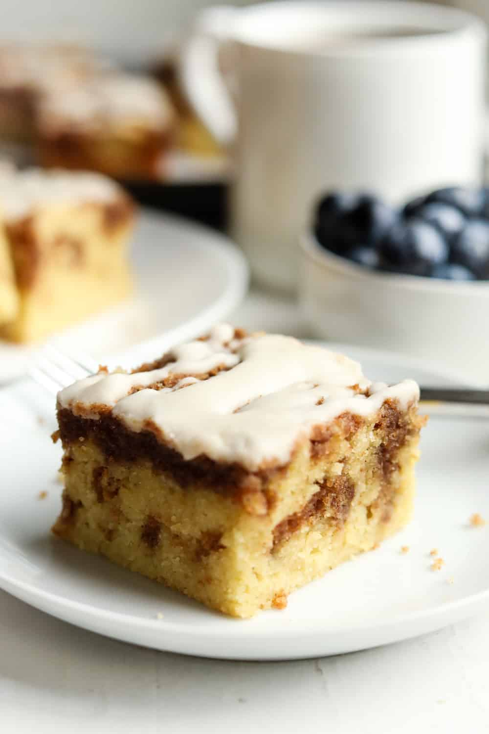 A piece of coffee cake on a white plate. There are more pieces in the background along with a cup of coffee and a bowl of blueberries.