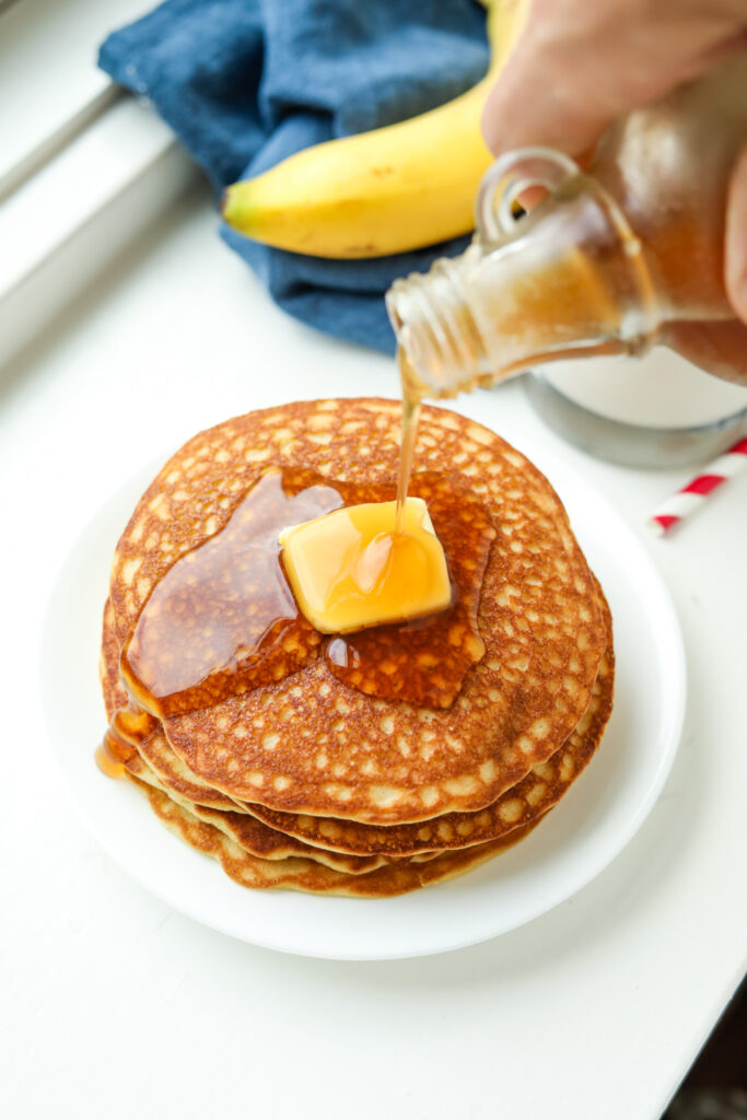 A stack of banana pancakes topped with butter and maple syrup being poured on them.