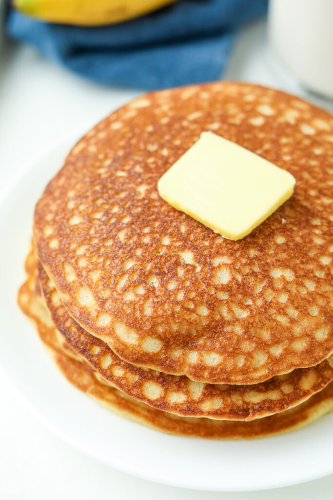 A stack of banana pancakes topped with butter on a white plate.