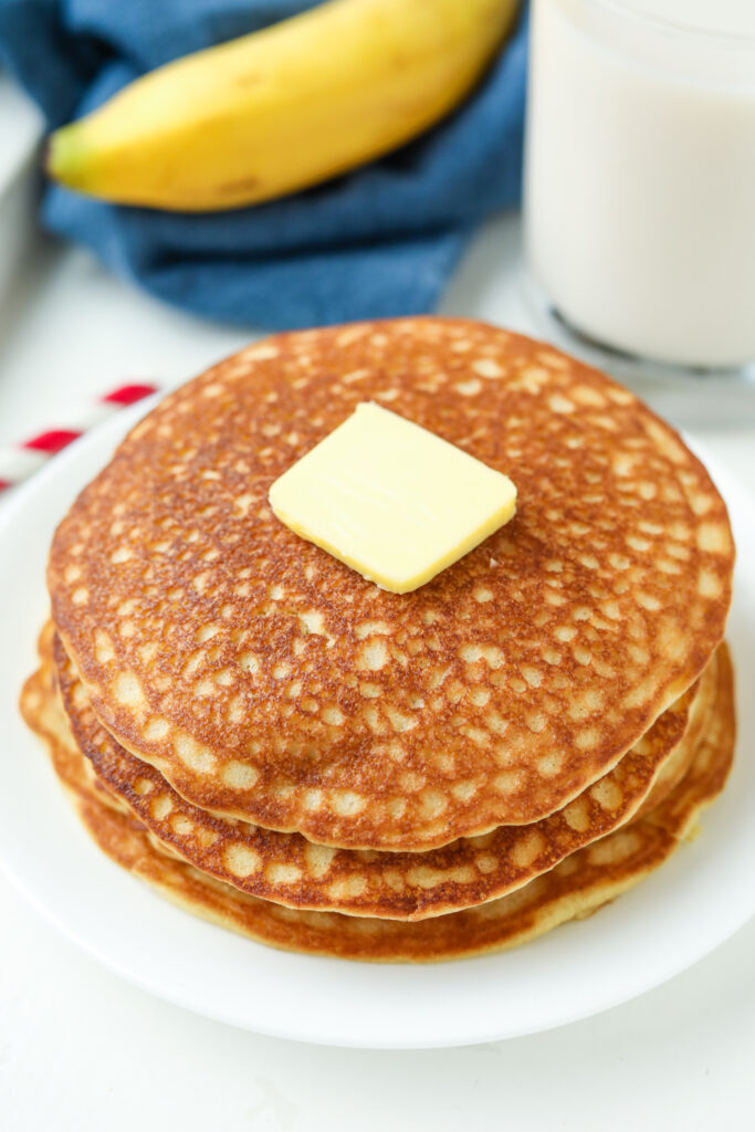 A stack of pancakes on a white plate topped with butter.