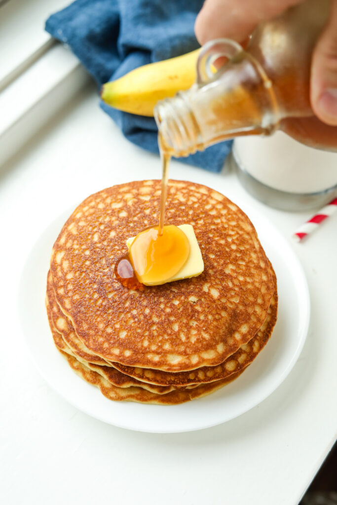 A stack of pancakes topped with butter and maple syrup is being poured on it.