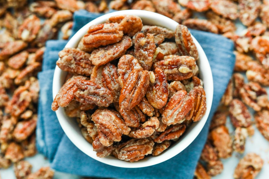 A white bowl filled with candied pecans. The bowl is set on a blue napkin and there are pecans all around the napkin.
