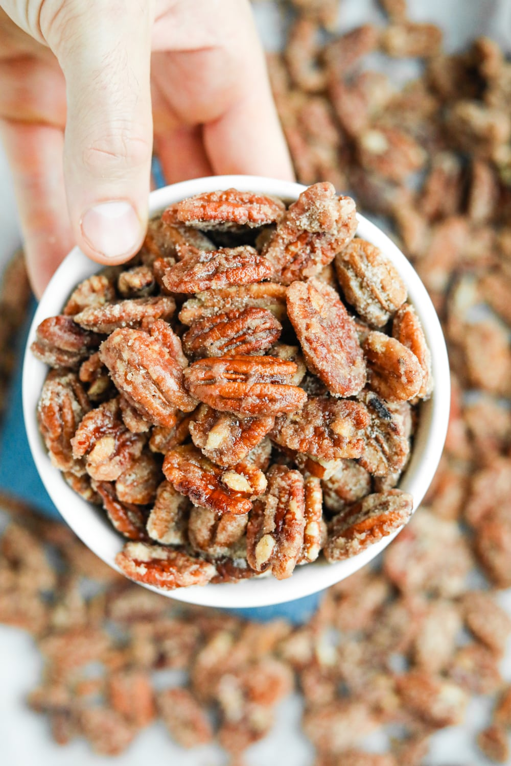 A hand holding a white bowl filled with candied pecans.