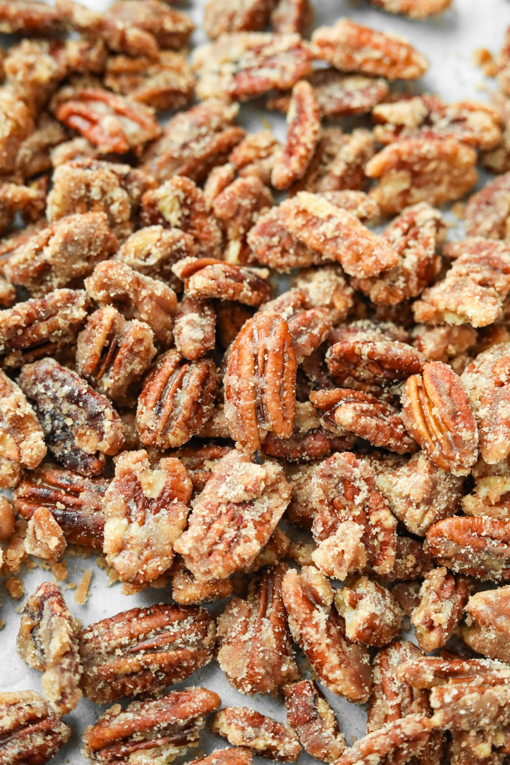 Candied pecans on a white sheet of parchment paper.