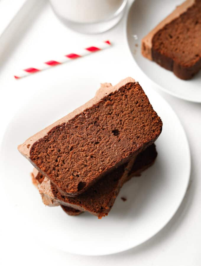 Three slices of chocolate yogurt cake stacked on top of one another on a white plate.