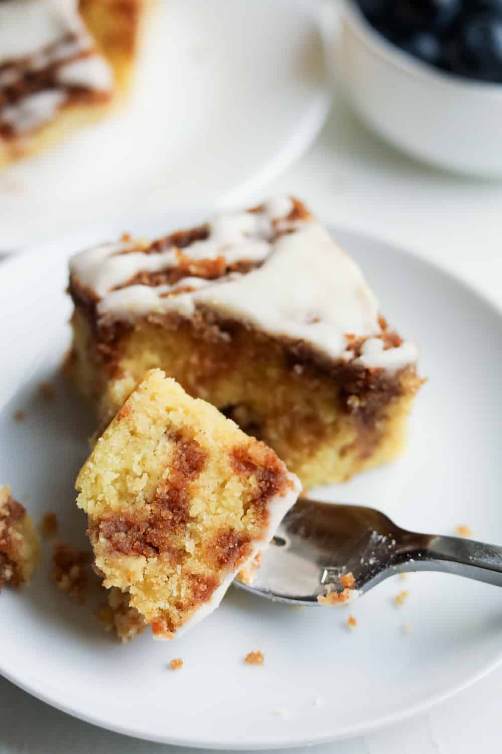 A fork holding a piece of coffee cake on a white plate.