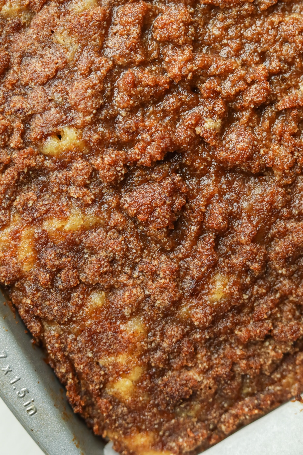A cake tray filled with cake that has a cinnamon crumble topping on it.