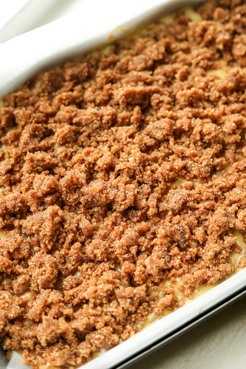 A cake tray filled with cake batter and a crumble topping.