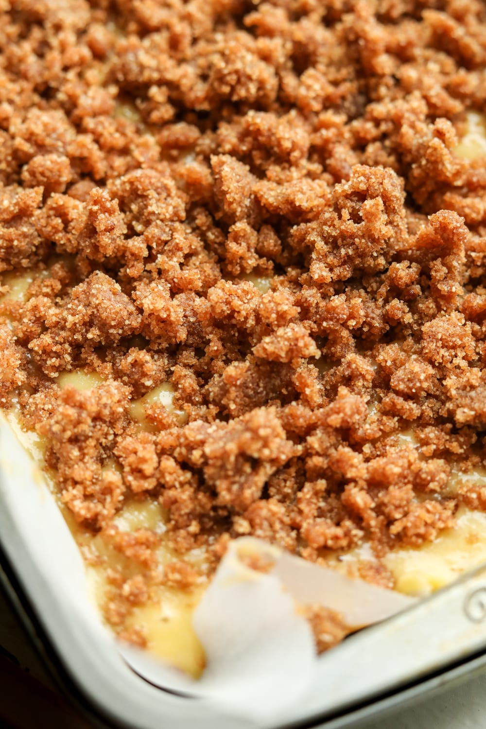 A cake tray filled with cake batter and a cinnamon crumble topping.