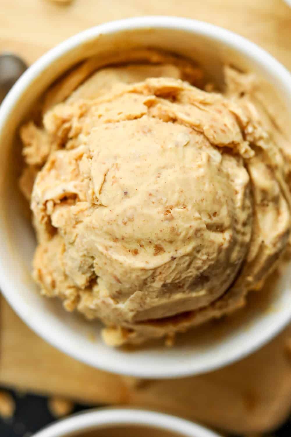 A white bowl filled with peanut butter ice cream on a wooden cutting board.