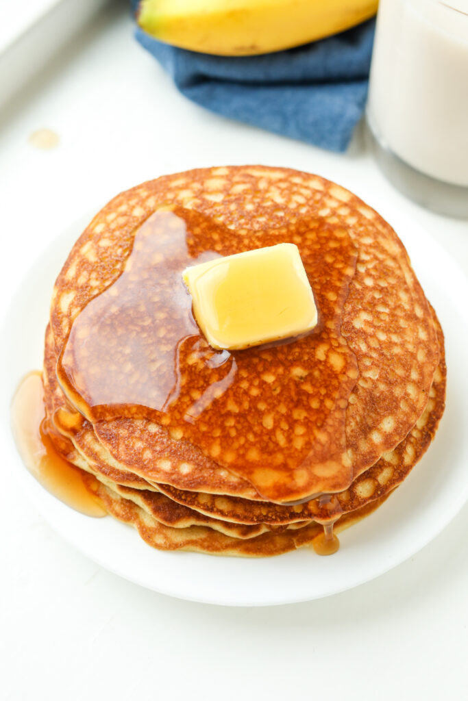 A stack of pancakes with covered in butter and maple syrup.