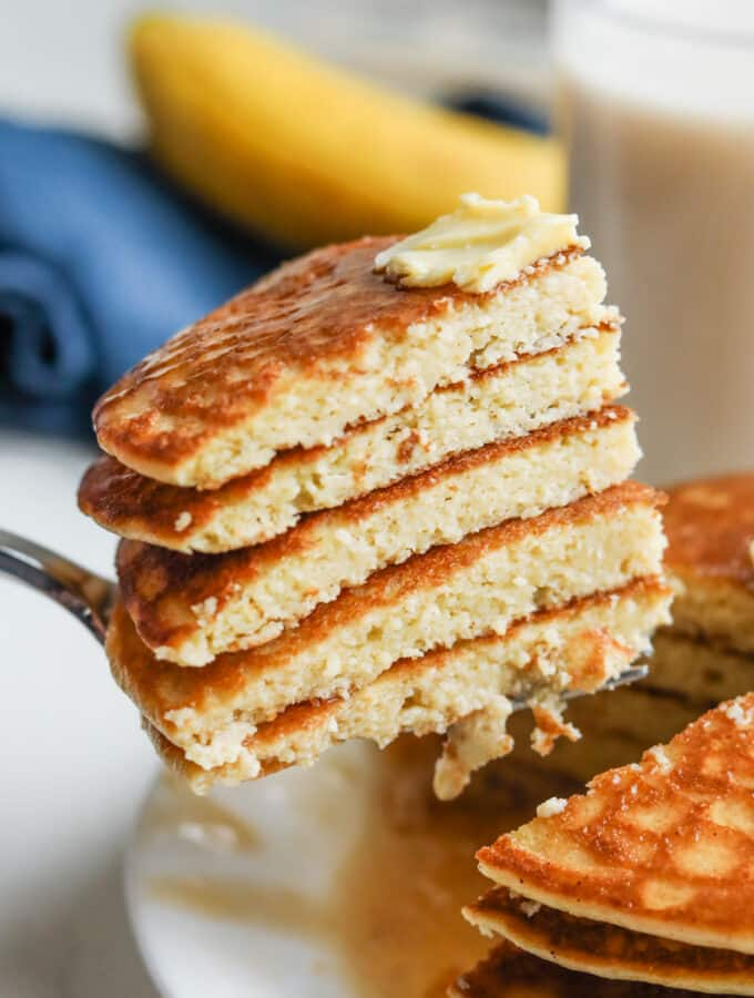 A fork pulling out a bunch cut up pancakes from a stack of them.