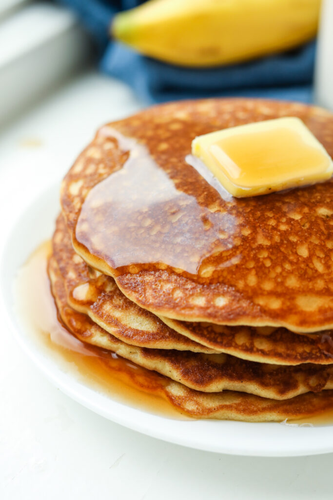The side of a stack of pancakes with maple syrup running off of them.