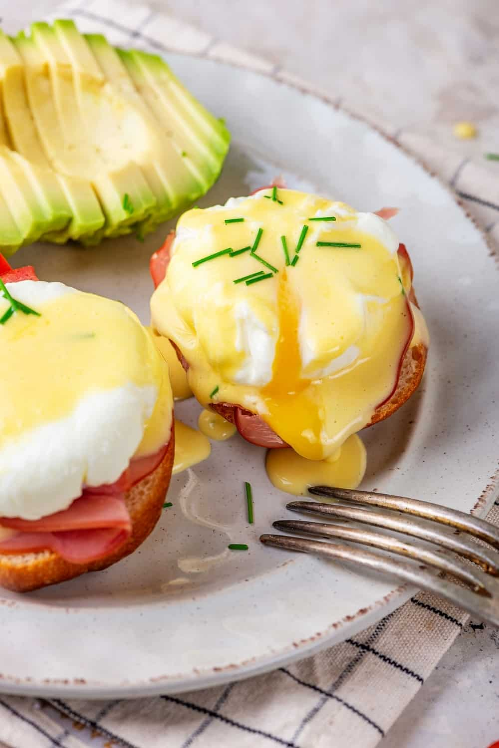 A white plate with the whole eggs Benedict and half of an eggs Benedict. There is a sliced avocado behind the eggs Benedict.
