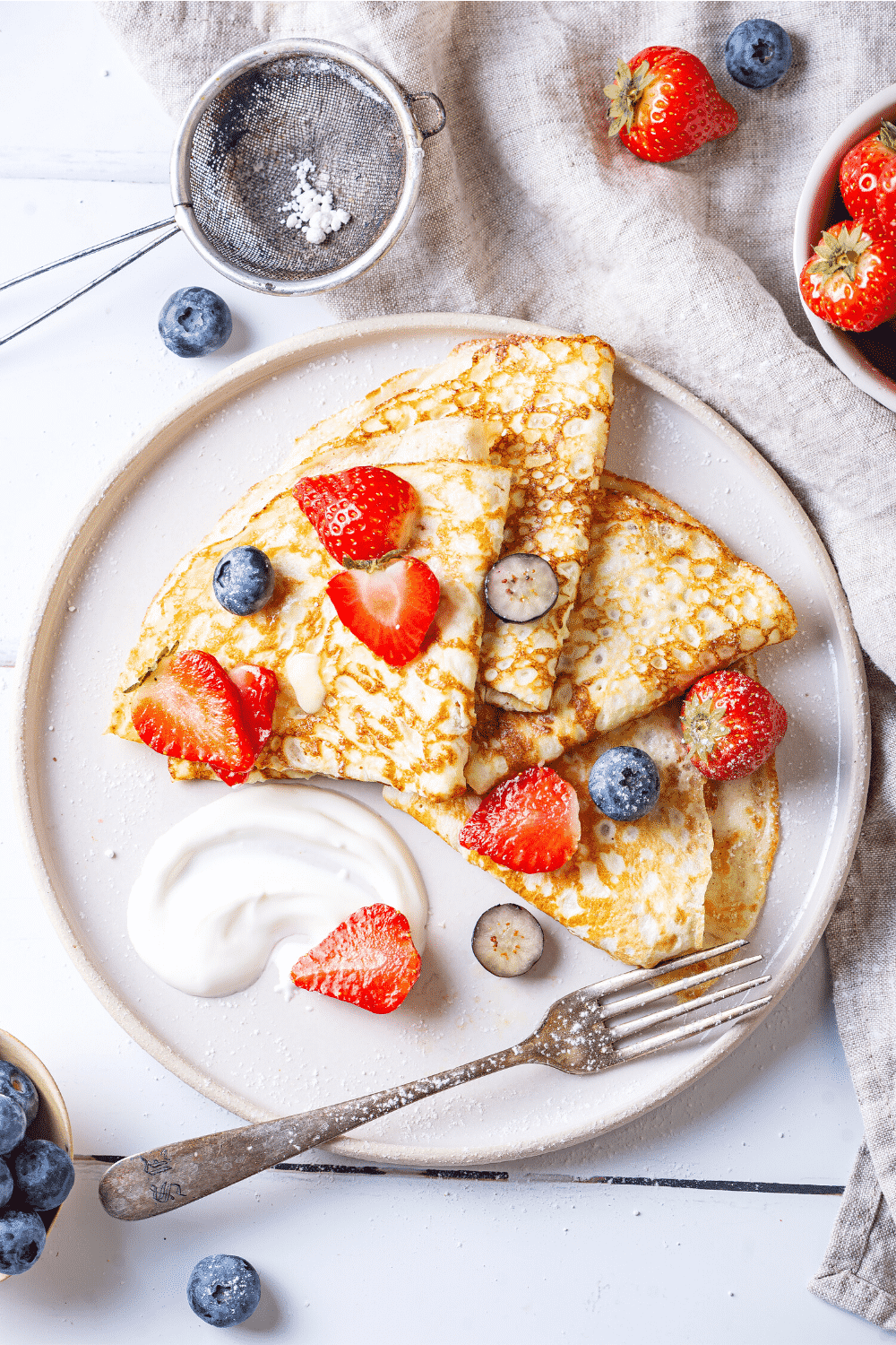 A white plate with four crepes on it. There are slices of blueberries and strawberries on the crepes.
