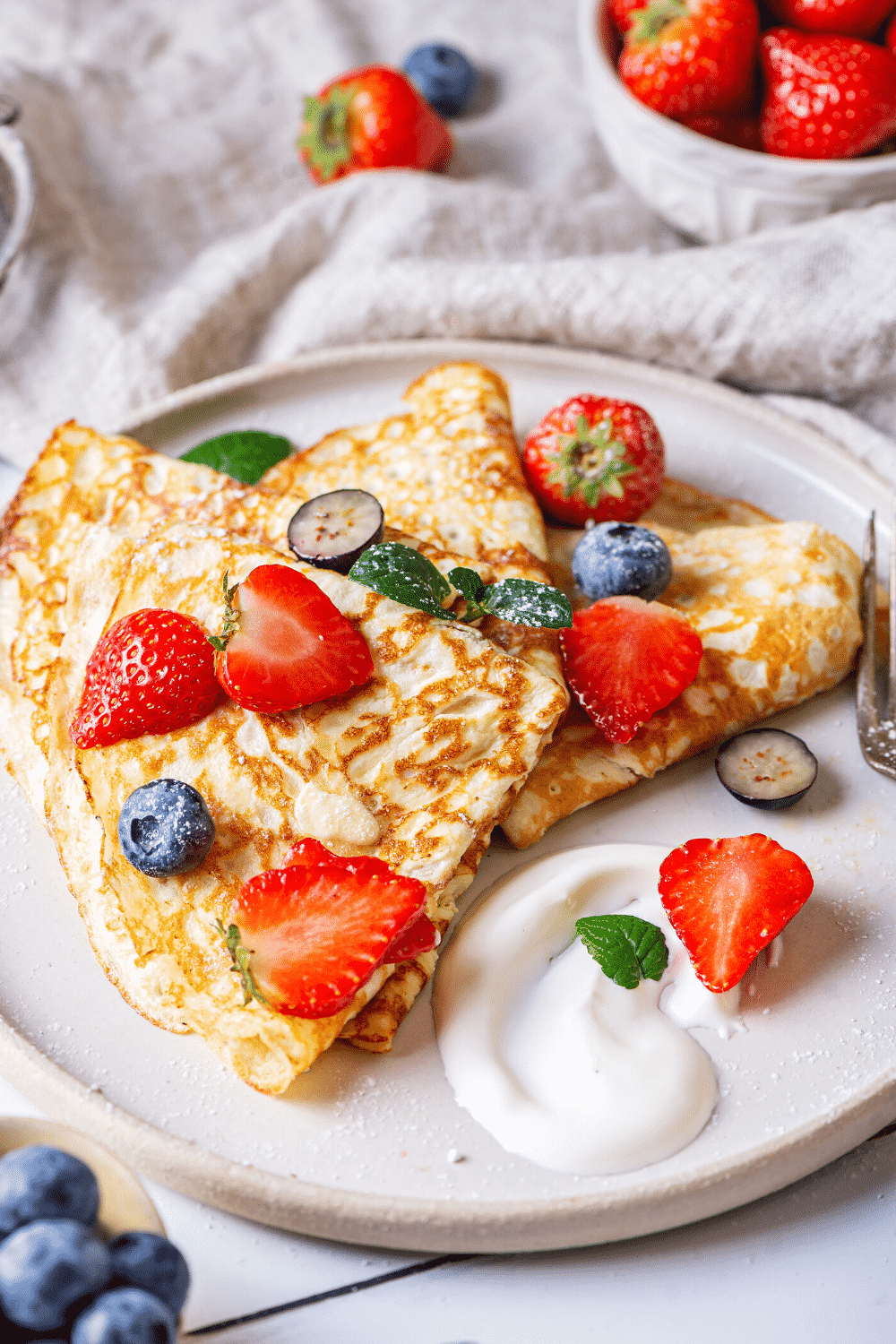 A white plate with a few crepes on it. There are slices of strawberries and a few blueberries on the crepes.