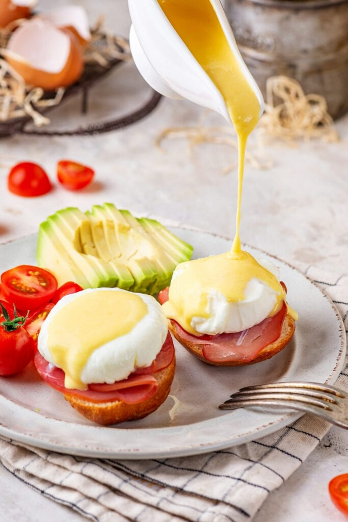 A white plate with two eggs Benedict on it. A gravy boat is pouring hollandaise sauce over top of the one eggs Benedict. There is a sliced avocado behind it and grape tomatoes to the left of the avocado.