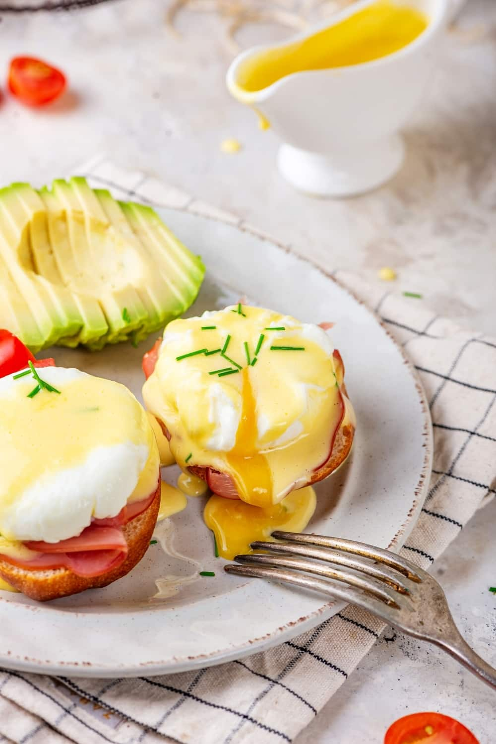 A white plate with two eggs Benedict on it. A sliced avocado is on the plate behind the eggs benedict.