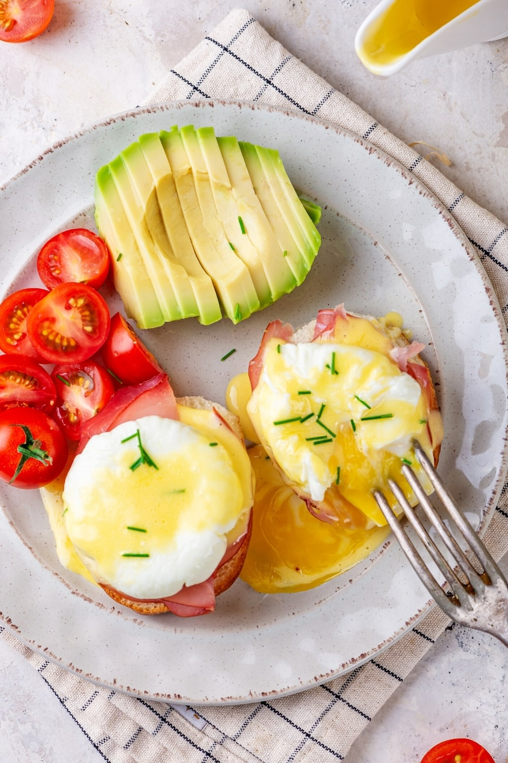A white plate with two eggs Benedict, a couple of sliced grape tomatoes, and a sliced avocado on it.