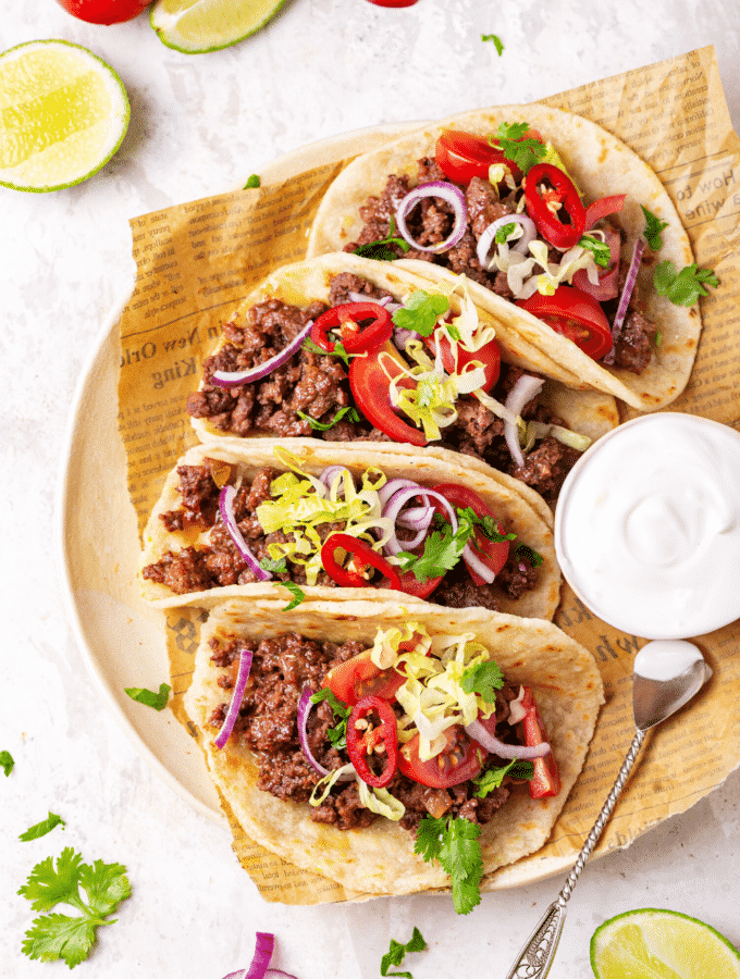 Four ground beef tacos in a row on a piece of newspaper on a plate. There is a small cup of sour cream to the right of the tacos.