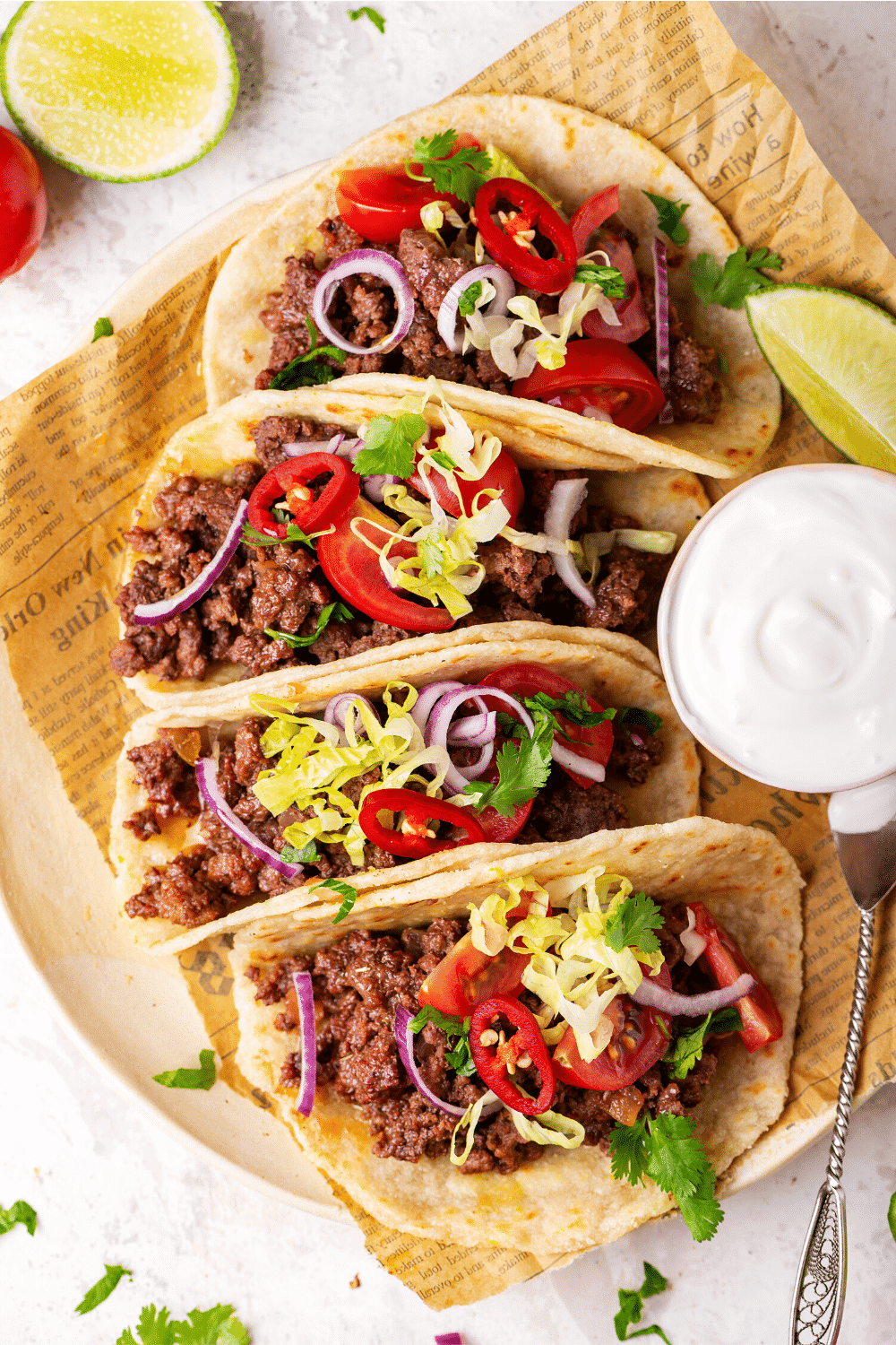 A row of four ground beef tacos on a piece of newspaper. To the right of the two middle tacos it's a small cup of sour cream.